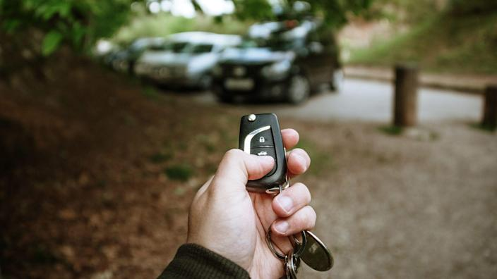 A human hand holding car keys to open a car.